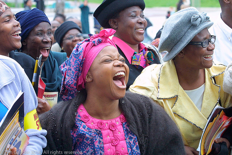 A group of black ladies laugh heartily at the end of a march in honour of murdered teenager Damilola taylor