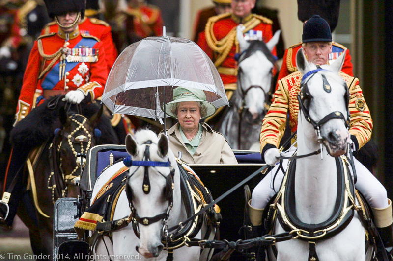 Queen Elizabeth II rides out in a horse-drawn carriage at the start of the Trooping the Colour ceremony and parade in London in 2001, protected by a transparent umbrella to protect her from the rain
