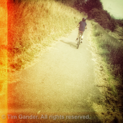 Hipster photo of boy on a bicycle on a cycle path, filtered with muted colours and orange light leaks