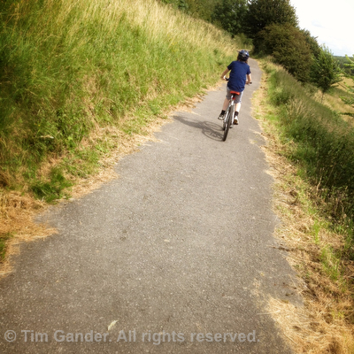 Angled photo of a boy on a bike on a cycle path