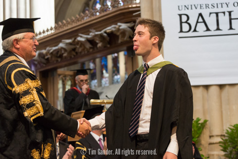 A graduate pokes his tongue out while shaking the hand of the Pro-Chancellor