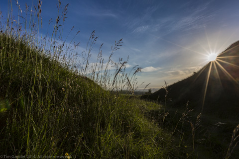 Scene of a section of Cley Hill, Wiltshire, at dusk with blue sky and the sun just touching the edge of the hill.