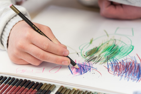 THe hand of a child colouring in with a pencil