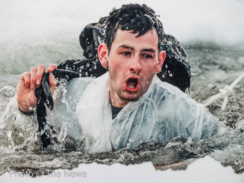 A Royal Marine reservist emerges from freezing arctic water as part of his training